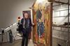 Rocco Mazzeo standing by a painting he is restoring