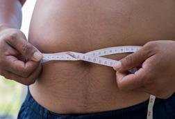A man measuring his waistline with a measuring tape