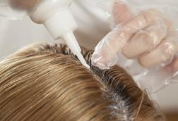 Close up image of hair dye being applied to blonde hair