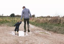 Father walking down muddy lane with child