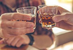 An image of two men clinking whiskey glasses