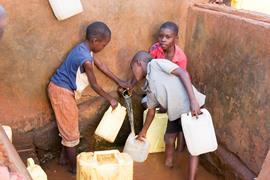 A group of Ugandan boys filling jerrycans with water in a local water well.