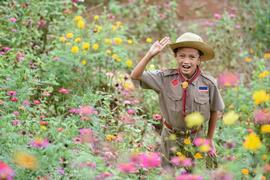 Cub scout surrounded by flowers