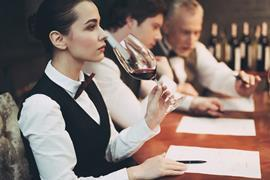 Sommelier smelling wine and taking notes