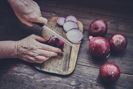 Chopping onions on a wooden board with a ceramic knife