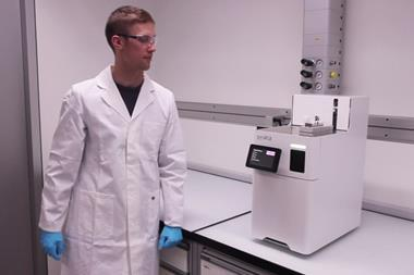 An image showing a chemist standing next to the Synple system