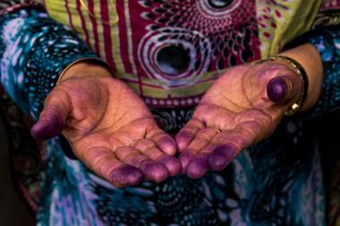A Bandari woman showing her hands with indigo traces after sewing a traditional burqa mask