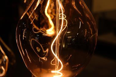 Close up of designer light installation, showing see through glass lamp and light bulb with filament illuminated.