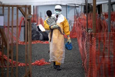 A Doctors Without Borders (MSF), health worker in protective clothing carries a child suspected of having Ebola