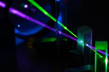 A photograph of green and blue lasers on optical table in physics laboratory