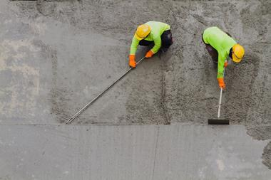 An image showing plasterer laying concrete cement with trowel