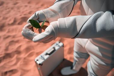 An image showing a cosmonaut standing on desert and holding sand with plant in palms