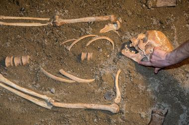 Human remains in sand being excavated by archaeologist