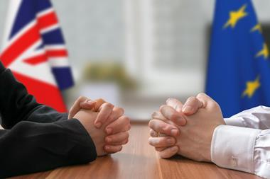 Two men facing each other at a table with EU and UK flags in the background