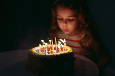 A picture of a little girl blowing candles on her birthday cake