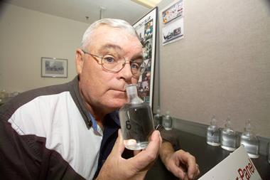 A photograph of George Aldrich sniffing a bottle of colourless liquid