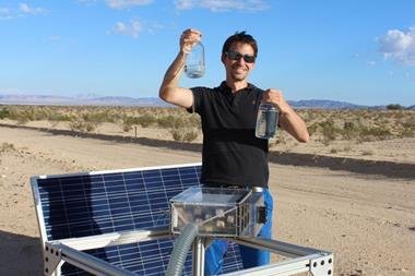 An image showing Mathieu Prévot displaying water collected by the harvester in the Mojave Desert