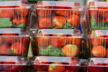 Strawberry berries in a plastic box ready for sale.