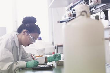 Female scientist in laboratory doing calculations