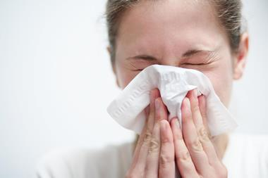 Woman blowing nose and sneezing into tissue