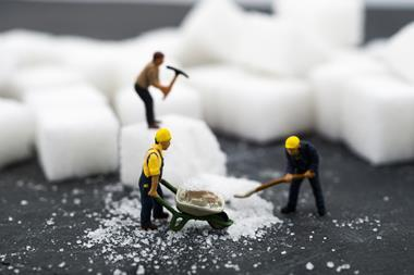 An image showing small human figurines working with blocks of sugar