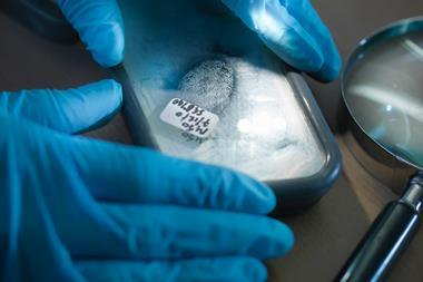 An image showing a close up of forensic scientist examining finger print in laboratory