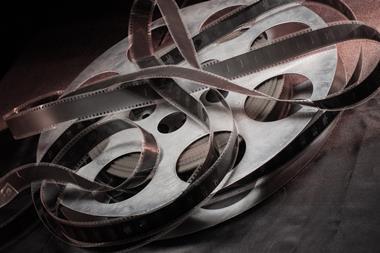 Movie reel lays on a black table