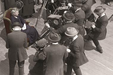 Marie Curie (circa 1915) with a group of cameramen on board a ship