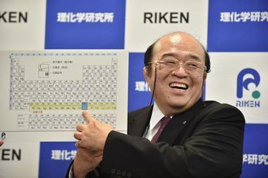An image showing Kosuke Morita smiling and pointing at element 113