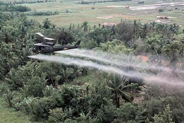 A UH- 1D helicopter from the 336th Aviation Company sprays a agent orange on a dense jungle area in the Mekong delta - Illustration