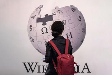 An image showing a woman standing in front of Wikipedia sign