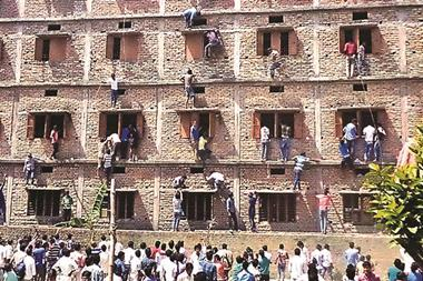 Relatives climbing exam building to help students pass exams, in Bihar, India, March 2015