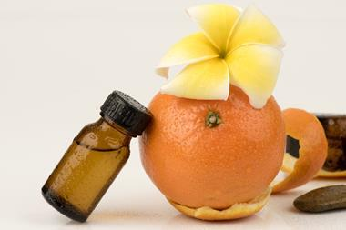 A photograph of orange peel and a bottle of essential oil