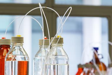 A close up photograph of clear and amber bottles with plastic hose for high performance liquid chromatography
