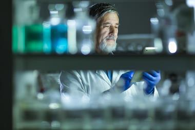 A man behind a shelf of chemicals recording data