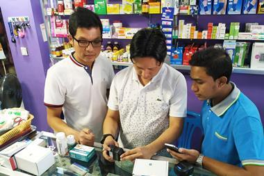 Image showing Pharmacists in Myanmar scanning medicines using RxAll's RxScanner