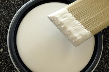 A photograph of a paintbrush and a tin of paint