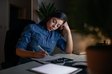 An image showing a young woman working late at night