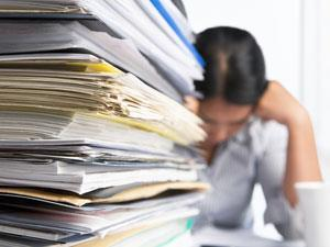 Stack of paperwork with overwhelmed lady