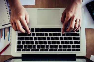An image showing a man's hands typing on a laptop keyboard