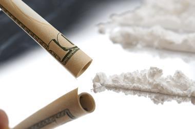 White powder being inhaled through a $10 note