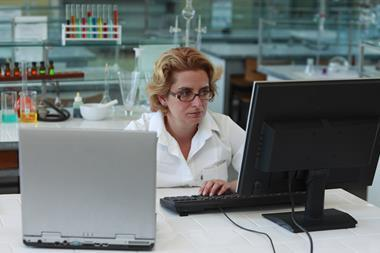 A photograph of a woman working on a computer in an organic chemistry laboratory