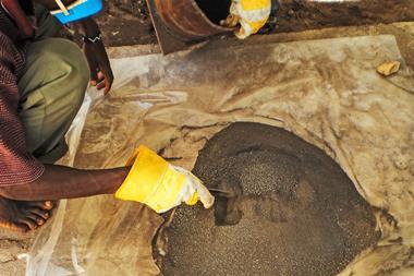 A man prods a pile of coltan ore