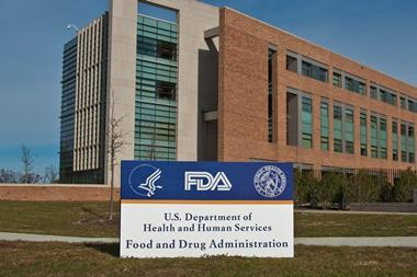 FDA Building 21 stands behind the sign at the FDA campus main entrance and houses the Center for Drug Evaluation and Research.