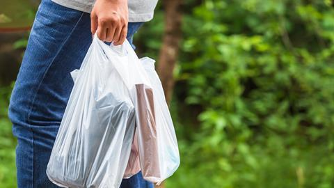 Woman holding a plastic bag with groceries
