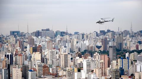 An image showing an aerial view of Sao Paulo and a helicopter in flight Brazil
