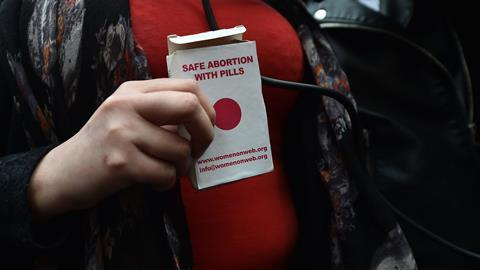 "An image showing the hands of a woman holding a packet that reads ""Safe abortion with pills"""