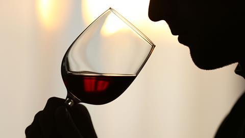 Silhouette man sniffing red wine