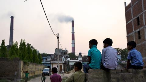 An image showing boys sitting and watching street cricket as emissions billow from smokestacks at the NTPC Ltd. Badarpur coal-fired power plant near residential property in Badarpur, Delhi, India