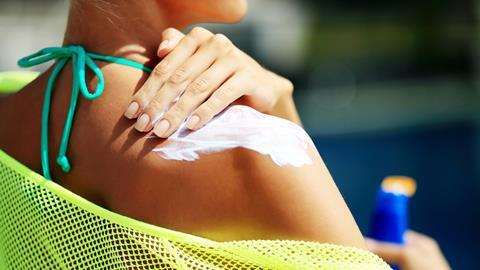 Picture of a woman applying sunscreen to shoulders